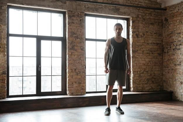 Konzentrierter junger sportler und ausruhen im fitnessstudio