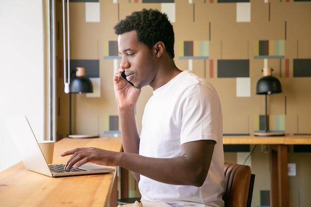 Konzentrierter junger unternehmer, der am laptop arbeitet und im gemeinsamen arbeitsbereich auf dem handy spricht