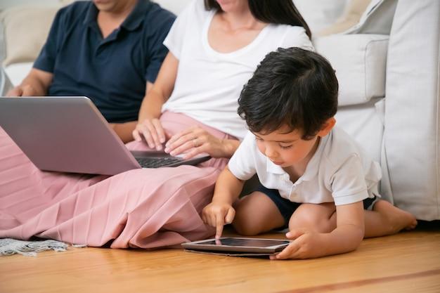 Konzentrierter kleiner junge, der das tablet alleine benutzt und von seinen eltern mit laptop auf dem boden im wohnzimmer sitzt.