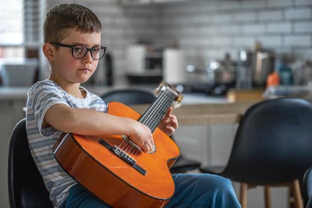 Konzentrierter kleiner junge, der zu hause in der küche mit einer gitarre in den händen sitzt.