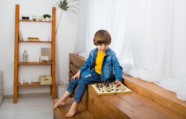 Konzentrierter kleiner junge sitzt in einem raum und spielt schach