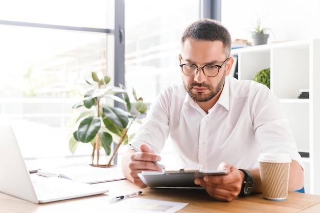 Konzentrierter kluger geschäftsmann 30s im weißen hemd, das zwischenablage mit papierdokumenten während der arbeit im büro hält und betrachtet