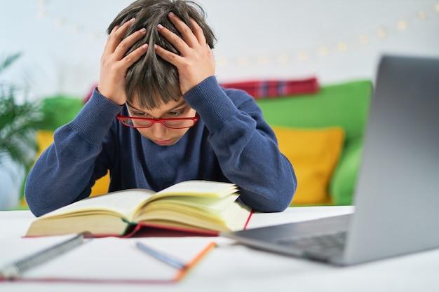 Konzentrierter kluger junge mit händen auf dem kopf liest in der schule ein buch mit online-unterricht, während er zu hause in quarantäne ist.