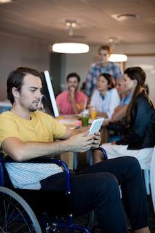 Konzentrierter körperlich behinderter mann auf rollstuhl mit tablette im büro