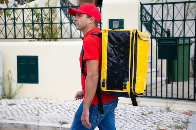 Konzentrierter kurier liefert ordnung und geht die straße entlang. professioneller lieferbote, der gelben rucksack trägt und nach erforderlicher adresse sucht. lieferservice und online-shopping-konzept