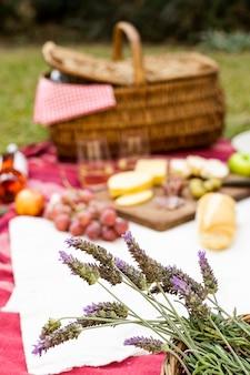 Konzentrierter lavendelstrauß neben picknick-leckereien