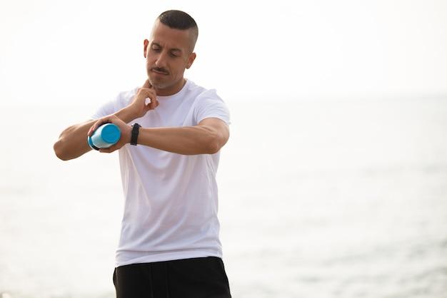 Konzentrierter männlicher athlet, der puls nimmt