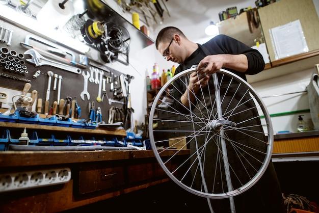 Konzentrierter mann, der ein korrektes werkzeug sucht, um fahrradrad zu reparieren.