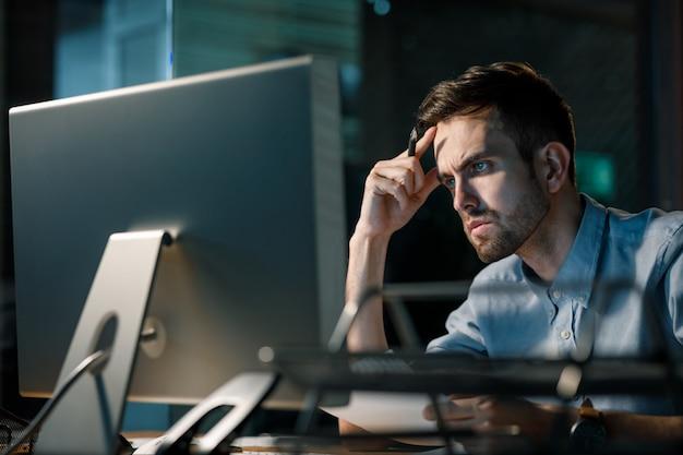 Konzentrierter mann, der im büro überarbeitet