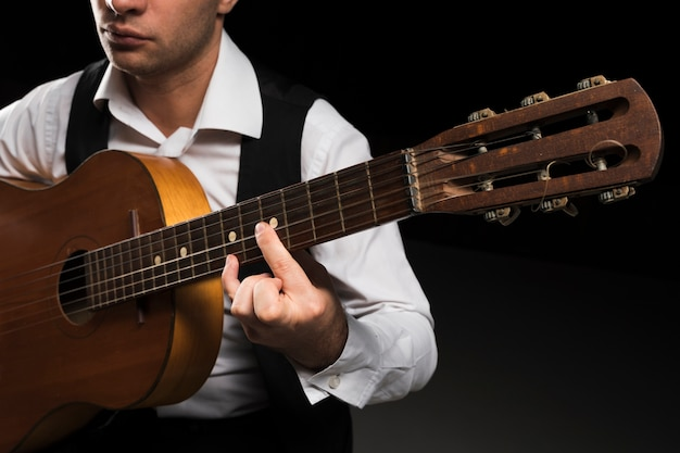 Konzentrierter mann, der noten auf gitarre spielt