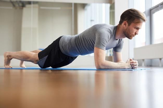 Konzentrierter mann, der plankenhaltung tut