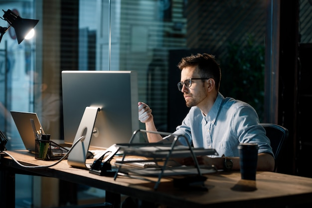 Konzentrierter mann, der spät mit computer arbeitet