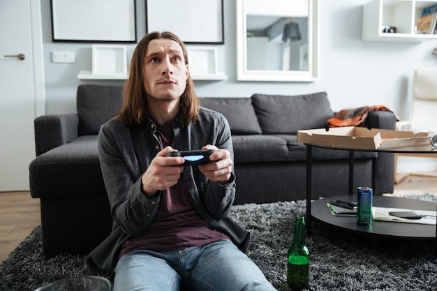Konzentrierter mann, der zuhause drinnen sitzt, spielt mit joystick