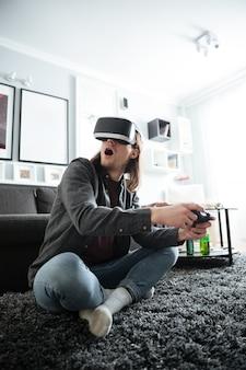 Konzentrierter mann, der zuhause drinnen sitzt, spielt