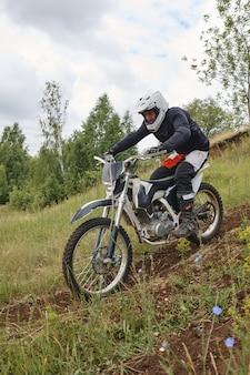 Konzentrierter mann im helm, der beim motorradfahren bergab gewicht zurückbekommt
