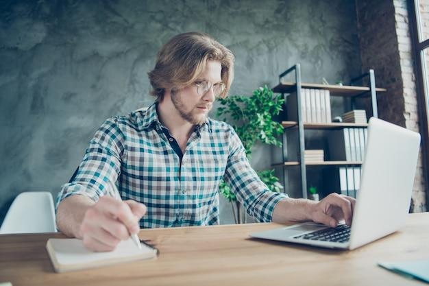 Konzentrierter mitarbeiter, der im büro am laptop arbeitet