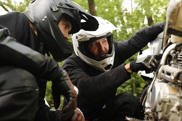 Konzentrierter motorradfahrer im helm zeigt auf den motor, während er mit einem freund im wald den grund für die motorradpanne herausfindet