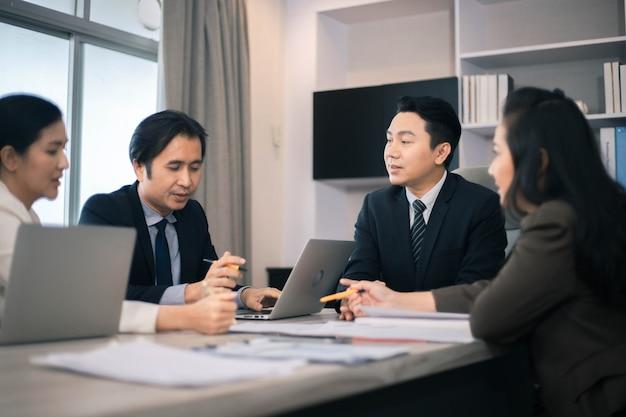 Konzentrierter multiethnischer mitarbeiter, der mit laptop-brainstorming beschäftigt ist und gedanken beim büromeeting teilt
