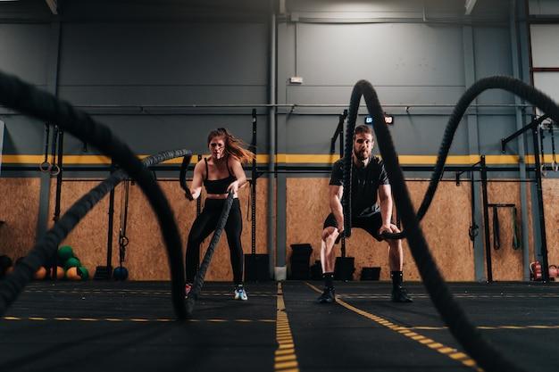 Konzentrierter, muskulöser junge und mädchen machen intensive kraftübungen im fitnessstudio mit einem schwarzen seil mit einem gewicht von 20 kilo.
