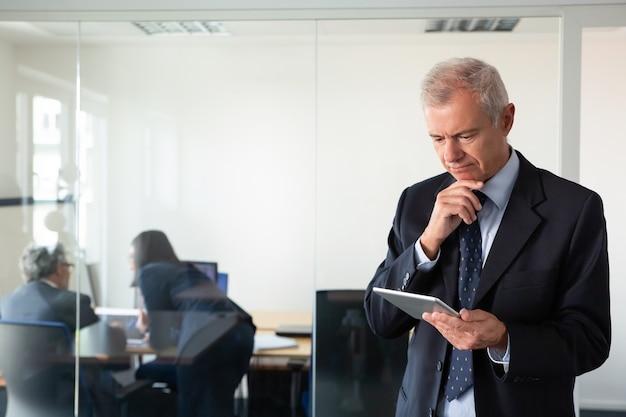 Konzentrierter nachdenklicher geschäftsmann, der auf tablet-bildschirm starrt, während seine kollegen projekt am arbeitsplatz hinter glaswand diskutieren. speicherplatz kopieren. kommunikationskonzept