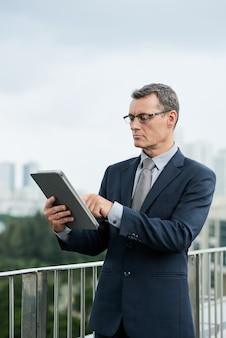 Konzentrierter reifer kaukasischer geschäftsmann im dunklen anzug, der auf dem balkon steht und ein digitales tablet verwendet