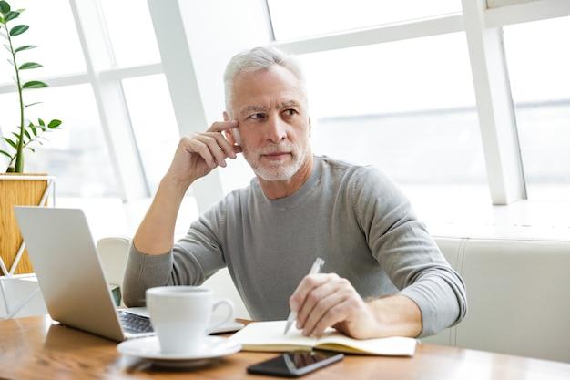 Konzentrierter reifer mann, der notizen macht und mit laptop arbeitet, während er drinnen im café sitzt