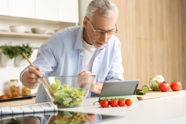 Konzentrierter reifer mann, der salat unter verwendung der tablette kocht