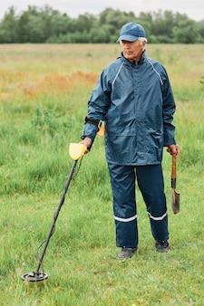 Konzentrierter reifer mann mit schaufel und metalldetektor, der münzen auf der wiese sucht