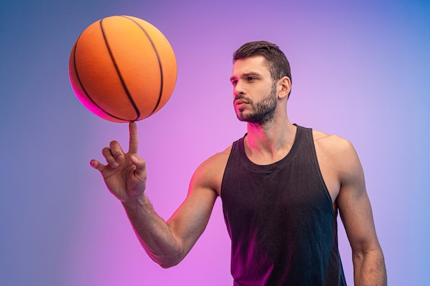 Konzentrierter sportler, der basketballball am finger dreht. junger bärtiger europäischer basketballspieler. getrennt auf blauem und rosa hintergrund. studioshooting