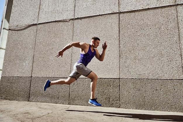 Konzentrierter starker sportlicher mann, der schnell auf der straße läuft.