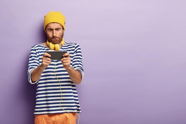 Konzentrierter stilvoller typ, der mit seinem telefon posiert