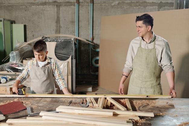 Konzentrierter teenager in der schürze, der mit holzstücken am schreibtisch steht und vater hilft, planke zu messen