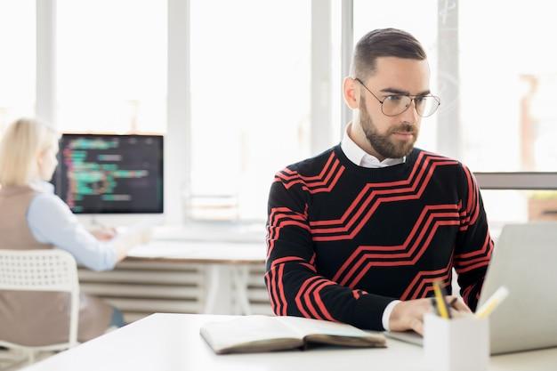 Konzentrierter texter, der mit laptop arbeitet