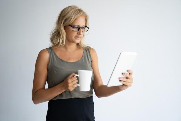 Konzentrierter trinkender kaffee des weiblichen freiberuflers und überprüfung von e-mail.