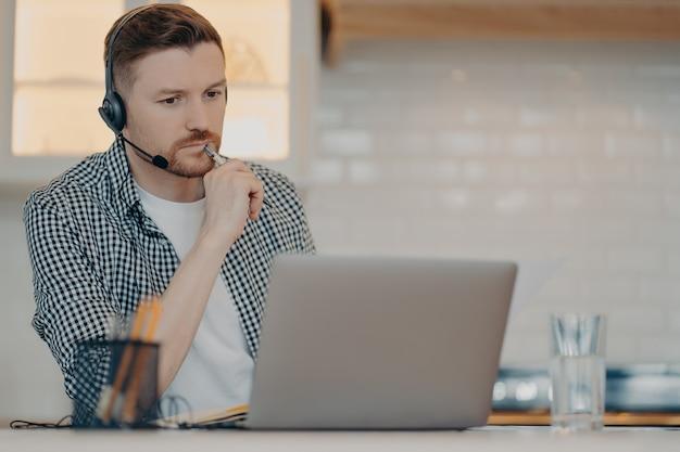 Konzentrierter typ, der auf den laptop-bildschirm schaut und den stift hält, während er videoanrufe mit kollegen hat oder im internet surft, männlicher freiberufler, der zu hause aus der ferne arbeitet, ernst und konzentriert bei der arbeit ist