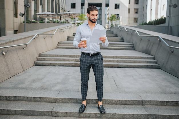 Konzentrierter und stilvoller junger mann steht auf stufen und schaut auf das dokument, das er in der hand hält. guy ist ernst und ruhig. er hat eine tasse kaffee in der rechten hand. junger mann ist mit gebäude umgeben.