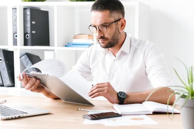 Konzentrierter unrasierter geschäftsmann 30s im weißen hemd, das zwischenablage mit papierdokumenten hält und betrachtet, während der arbeit im büro