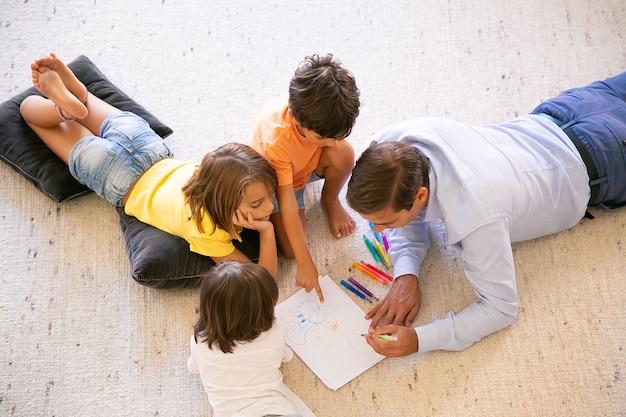 Konzentrierter vater und kinder, die auf teppich liegen und kritzeleien malen. vater mittleren alters, der mit bunten stiften zeichnet und mit niedlichen kindern zu hause spielt. konzept für kindheit, spielaktivität und vaterschaft