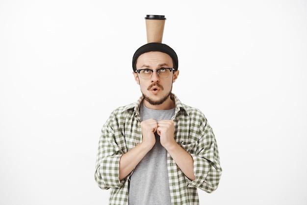 Konzentrierter verspielter lustiger europäischer mann mit bart in gläsern und mütze, die palmen nahe brust intensiv und besorgt mund öffnen und pappbecher mit kaffee auf kopf balancierend hält