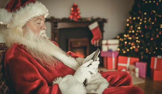 Konzentrierter weihnachtsmann mit smartphone zu weihnachten