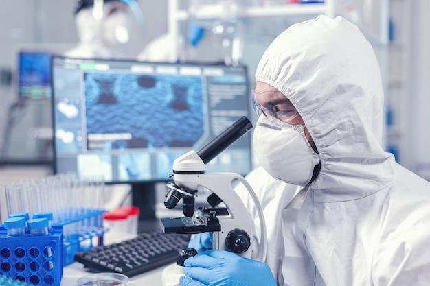 Konzentrierter wissenschaftler in der ppe-ausrüstung, der das mikroskop im labor untersucht. wissenschaftler im schutzanzug, der während der globalen epidemie am arbeitsplatz mit moderner medizintechnik sitzt.
