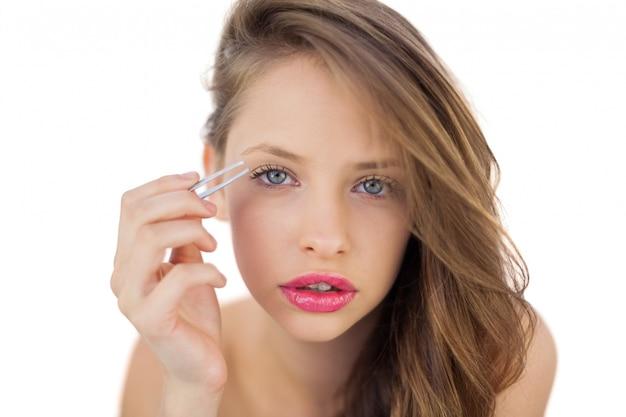 Konzentriertes brunettemodell, das ihre augenbrauen zupft
