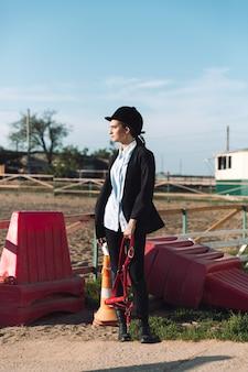 Konzentriertes junges cowgirl, das draußen steht