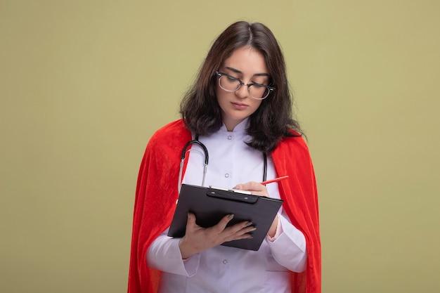 Konzentriertes junges kaukasisches superheldenmädchen in rotem umhang mit arztuniform und stethoskop mit brille, die mit bleistift auf zwischenablage schreibt