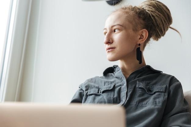 Konzentriertes junges mädchen mit dreadlocks und piercing drinnen mit laptop-computer.
