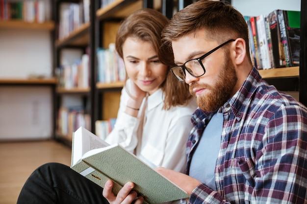 Konzentriertes junges paar, das buch in der bibliothek liest