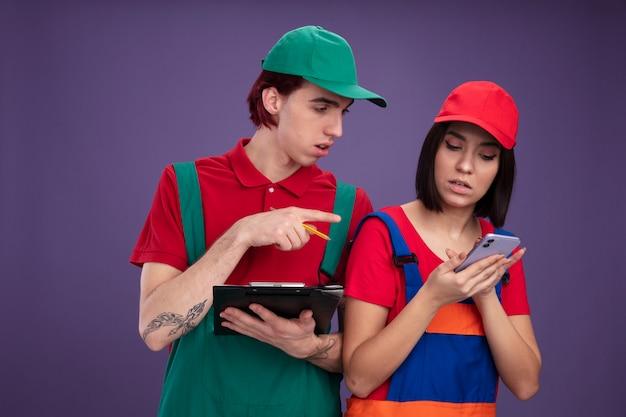 Konzentriertes junges paar in bauarbeiteruniform und mütze mit bleistift und klemmbrett mädchen mit handy-typ, der auf das handy zeigt und auf lila wand schaut