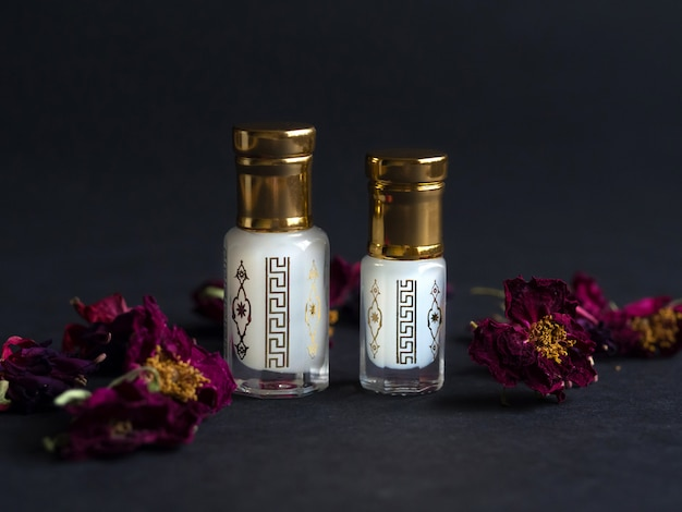 Konzentriertes parfüm in einer miniflasche auf dem schwarzen hintergrund.
