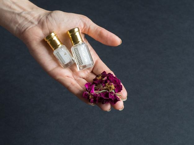 Konzentriertes parfüm in einer miniflasche auf dem schwarzen tisch.