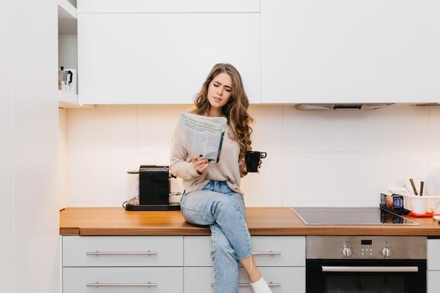 Konzentriertes reizendes mädchen, das zeitschrift liest, während tee genießt